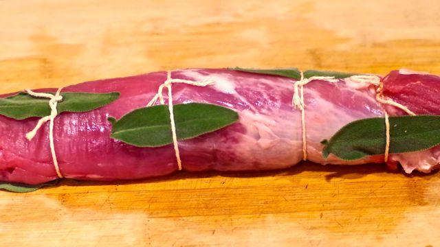 Fresh sage leaves are tucked under kitchen twine wrapped around pork.