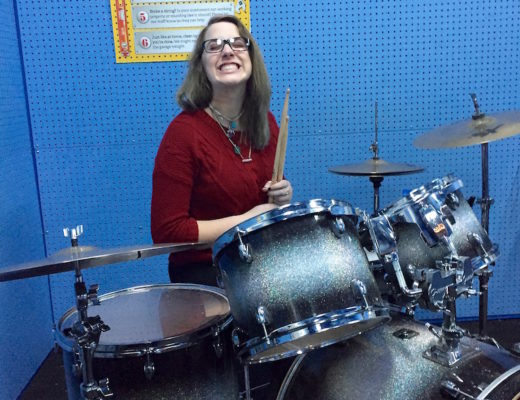 Teaching moments often happen unexpectedly. Rose experiments on drums at the Fort Collins Discovery Center in a simulated garage band exhibit. December 2015. Photo credit: Gail Goodman.